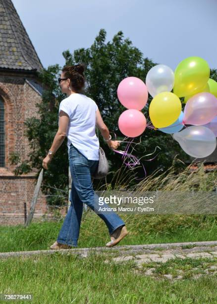 Rear View Of Woman Holding Balloons While Walking At Footpath