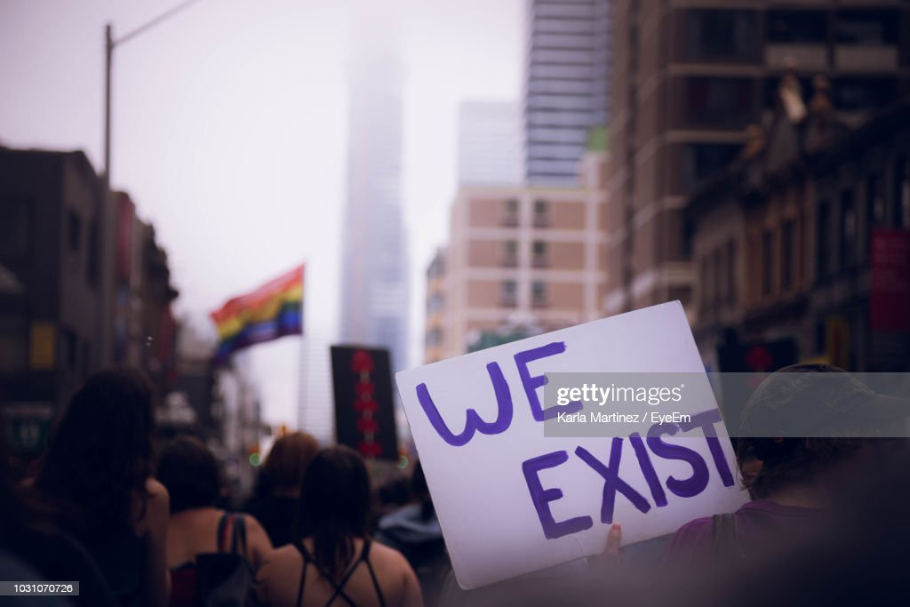 Rear View Of Woman Holding Banner With Message Amidst Crowd During Protest : Stock Photo