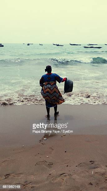 Rear View Of Woman Holding Basket While Standing On Shore Against Clear Sky