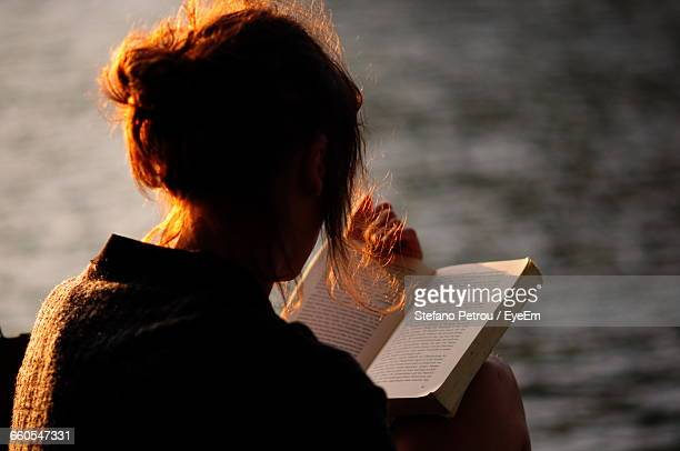 rear view of woman holding book against lake - literature ストックフォトと画像