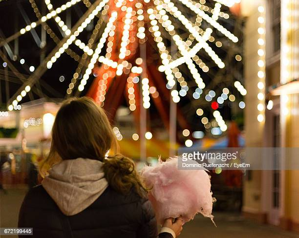 Rear View Of Woman Holding Cotton Candy Against Illuminated Ferris Wheel At Night