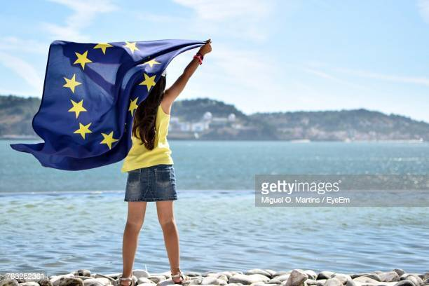 Rear View Of Woman Holding European Union Flag While Standing At Beach Against Sky