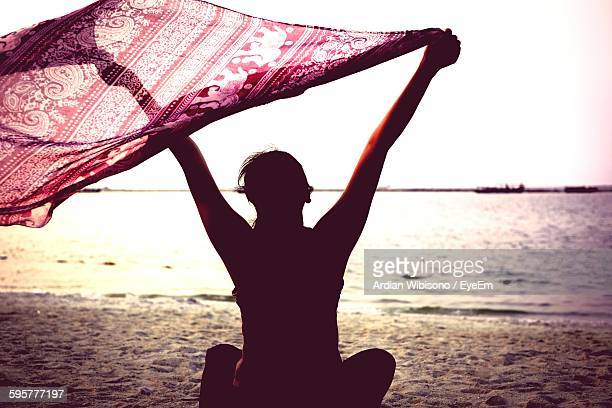 Rear View Of Woman Holding Fabric While Sitting On Beach Against Sky