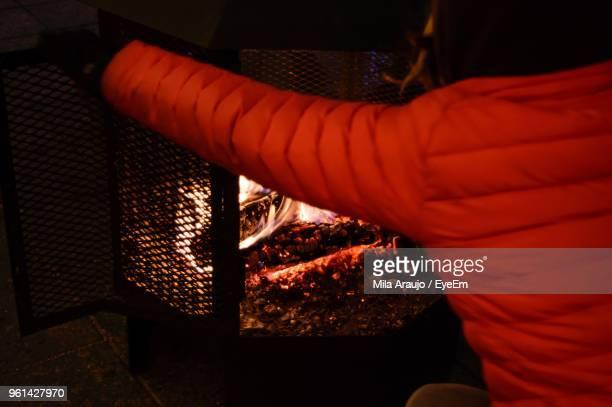 Rear View Of Woman Holding Fire Pit At Home