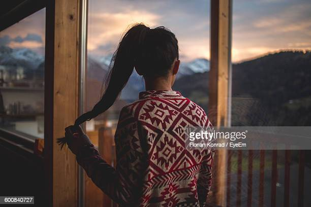Rear View Of Woman Holding Hair Standing At Balcony During Sunset