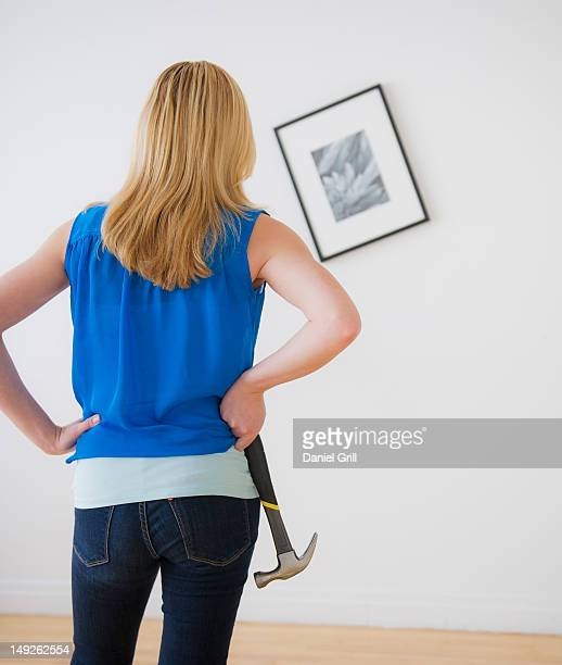 Rear view of woman holding hammer and looking at painting on wall