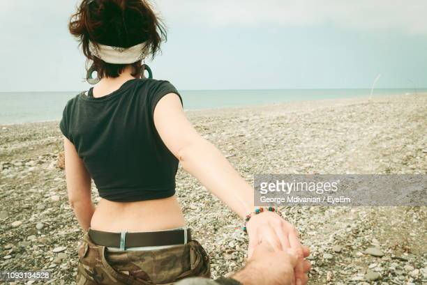 rear view of woman holding hand while walking at beach - クロップトップ ストックフォトと画像