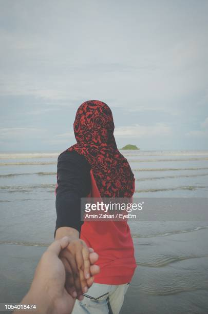 Rear View Of Woman Holding Hands With Man On Beach Against Sky