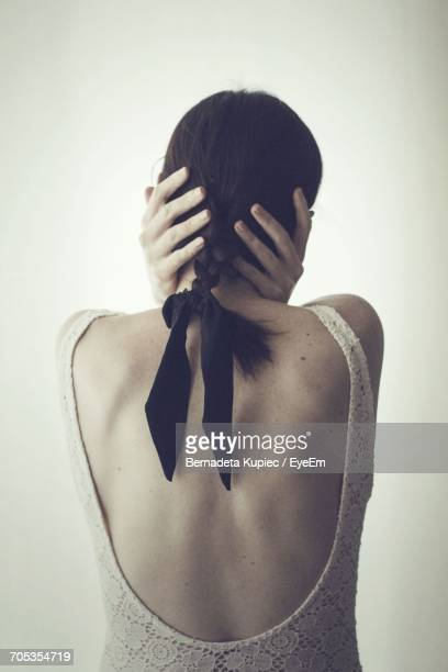Rear View Of Woman Holding Head While Standing By Wall At Home