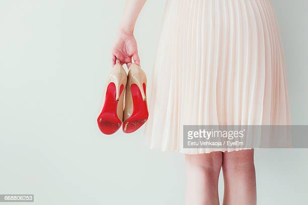 rear view of woman holding high heels against wall - hoge hakken stockfoto's en -beelden