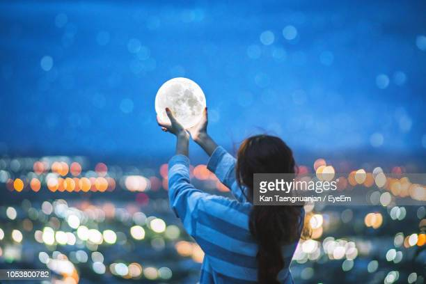 rear view of woman holding lighting equipment in illuminated city at night - moonlight stock pictures, royalty-free photos & images