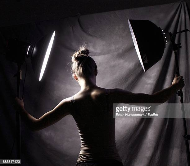 rear view of woman holding lighting equipment in studio - photo shoot photos et images de collection