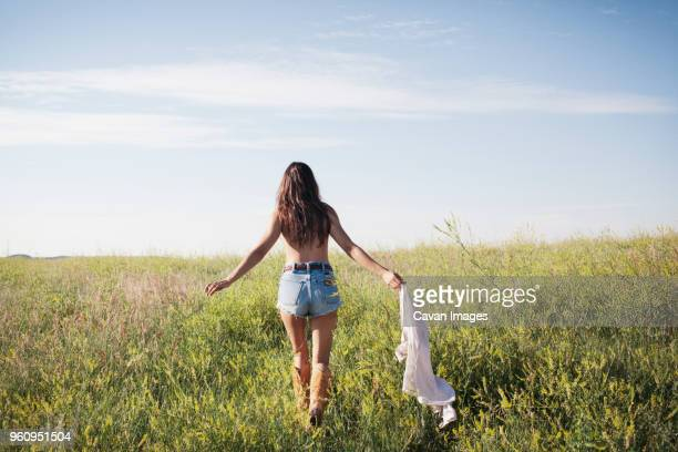 Rear view of woman holding shirt and walking on grassy field against sky