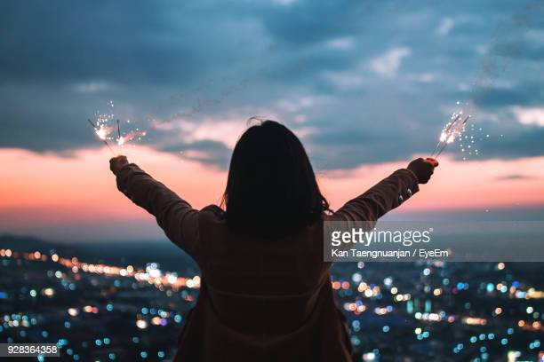 Rear View Of Woman Holding Sparklers Against Illuminated Cityscape At Dusk