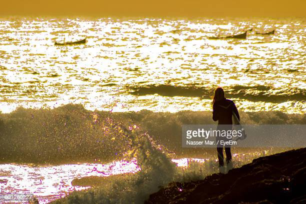 Rear View Of Woman Holding Surfboard Against Sea