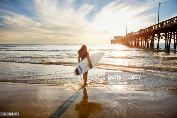 Rear view of woman holding surfboard and standing on shore