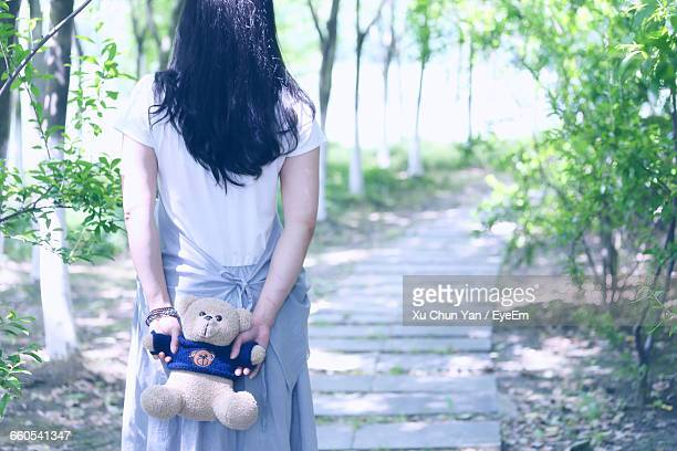 Rear View Of Woman Holding Teddy Bear Behind Back While Walking On Walkway In Park