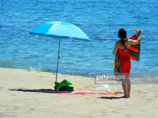 Rear View Of Woman Holding Towel While Standing At Beach