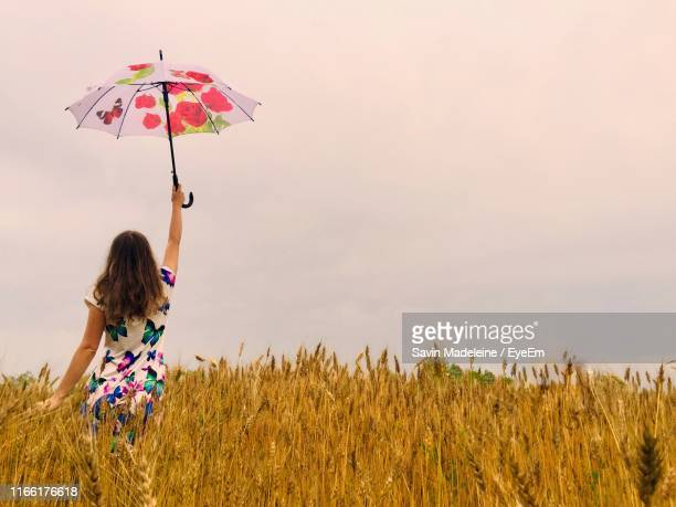 rear view of woman holding umbrella while standing amidst plants against clear sky - lady madeleine stock-fotos und bilder