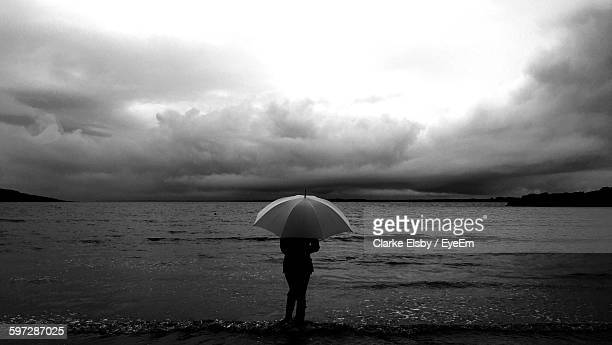 Rear View Of Woman Holding Umbrella While Standing By Sea Against Cloudy Sky