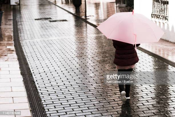 rear view of woman holding umbrella while walking on footpath - monsoon stock pictures, royalty-free photos & images