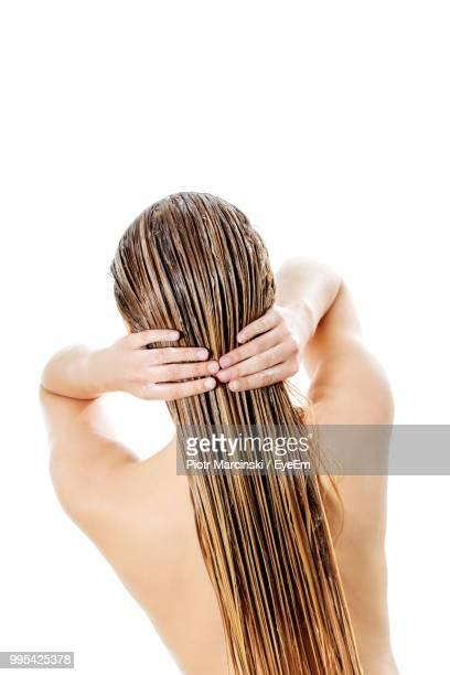 rear view of woman holding wet hair against white background - wet hair stock pictures, royalty-free photos & images