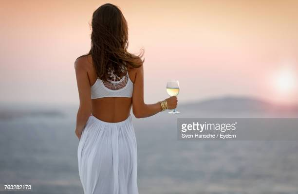 rear view of woman holding wineglass while standing against aegean sea during sunset - ver a hora stockfoto's en -beelden