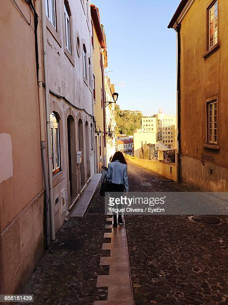 Rear View Of Woman In Alley In Old Rustic City