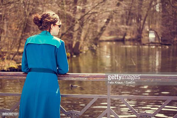 rear view of woman in blue trench coat standing by lake during sunny day - トレンチコート ストックフォトと画像
