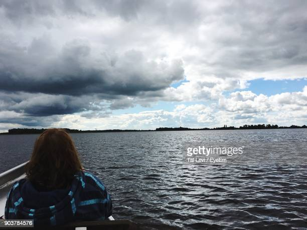 Rear View Of Woman In Boat At Sea Against Sky