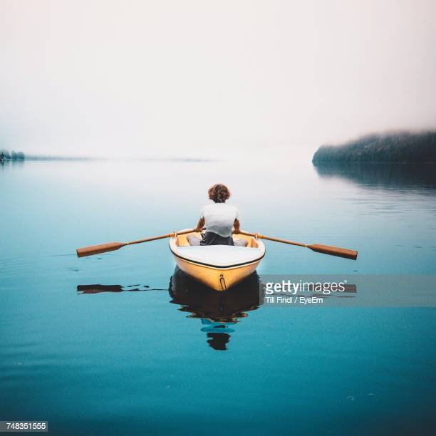 rear view of woman in boat on sea against clear sky - ruhige szene stock-fotos und bilder