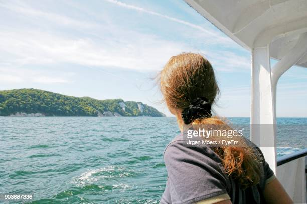 Rear View Of Woman In Boat On Sea Against Sky
