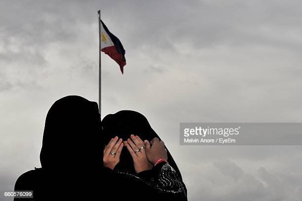 Rear View Of Woman In Burka Consoling Friend Against Philippines Flag