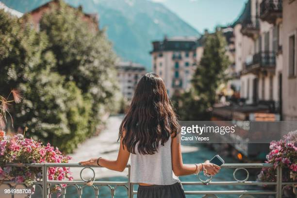 rear view of woman in chamonix-mont blanc village and french alps - francia foto e immagini stock