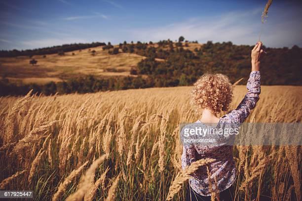 rear view of woman in farm field against sky - bortes stock-fotos und bilder