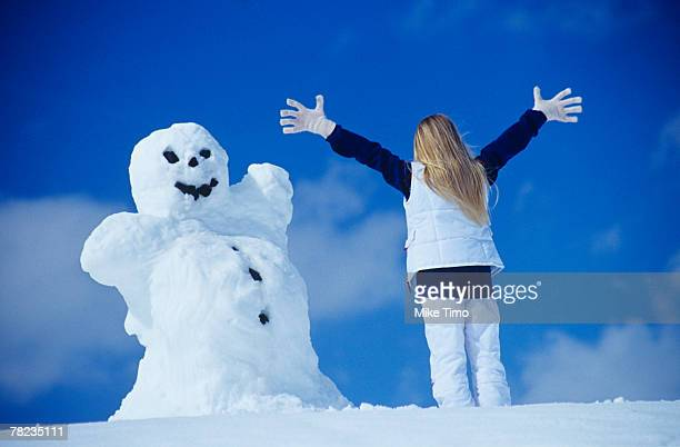 rear view of woman in front of snowman - sport d'hiver photos et images de collection