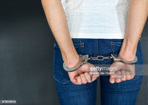 rear view of woman in handcuffs - arrest stock pictures, royalty-free photos & images