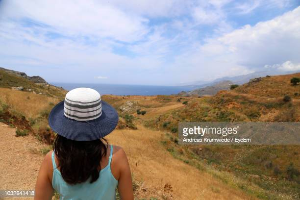 Rear View Of Woman In Hat At Beach Against Sky