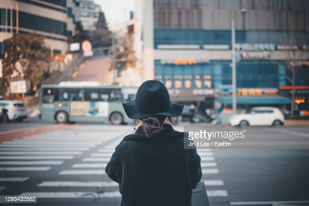 rear view of woman in hat standing on city street - south korea stock pictures, royalty-free photos & images