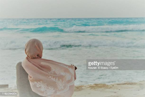 rear view of woman in headscarf looking at sea - religious veil stock pictures, royalty-free photos & images