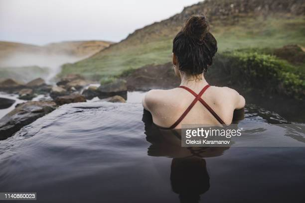 rear view of woman in hot pool iceland - hot spring stock pictures, royalty-free photos & images