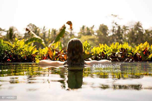 Rear View Of Woman In Infinity Pool Against Plants