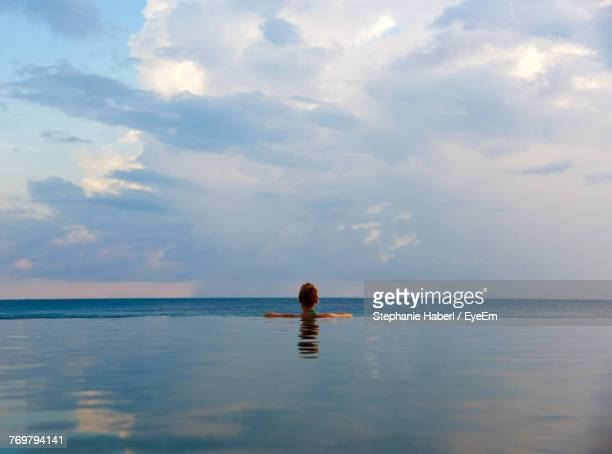 rear view of woman in infinity pool by sea against cloudy sky - infinity pool foto e immagini stock