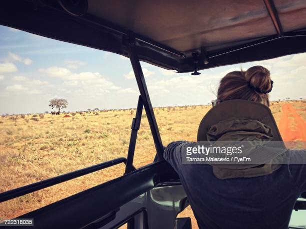 rear view of woman in off-road vehicle at tsavo east national park - áfrica del este fotografías e imágenes de stock