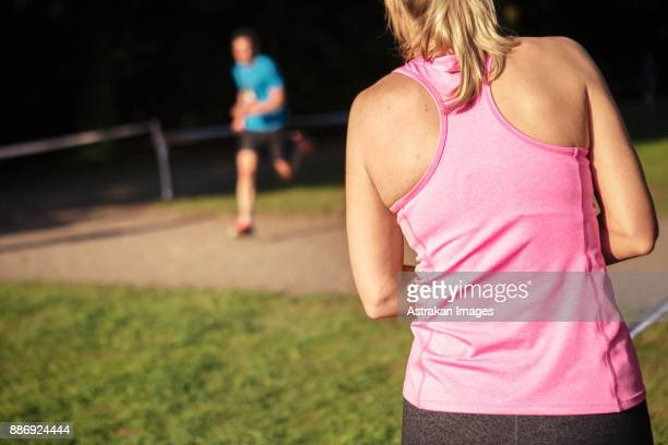 rear view of woman in pink tank top - vest stock photos and pictures