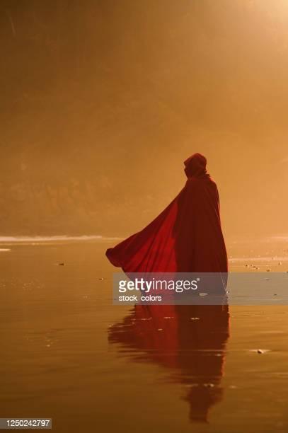 achtermening van vrouw in rode kaap - cape stockfoto's en -beelden