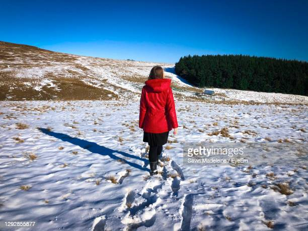 rear view of woman in red coat walking on a field covered in snow - lady madeleine stock-fotos und bilder