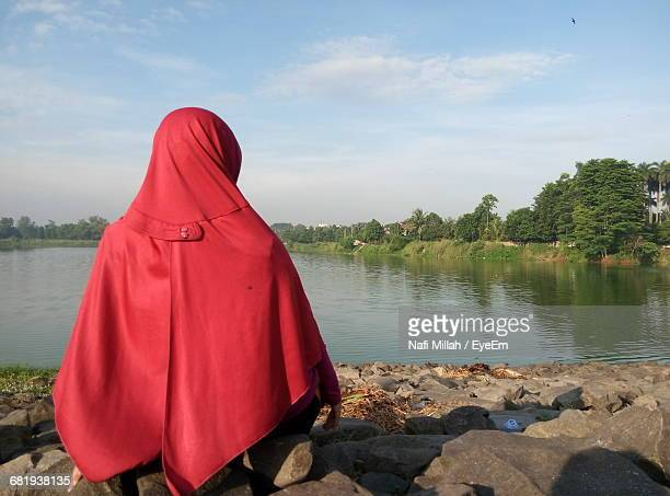 Rear View Of Woman In Red Hijab Sitting At Riverbank Against Sky