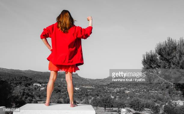 Rear View Of Woman In Red Jacket Gesturing Fist While Standing Towards Landscape Against Sky