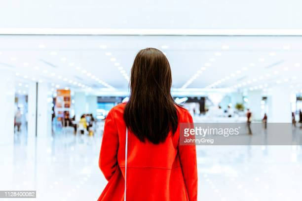 rear view of woman in red jacket in shopping mall - mystery stock pictures, royalty-free photos & images